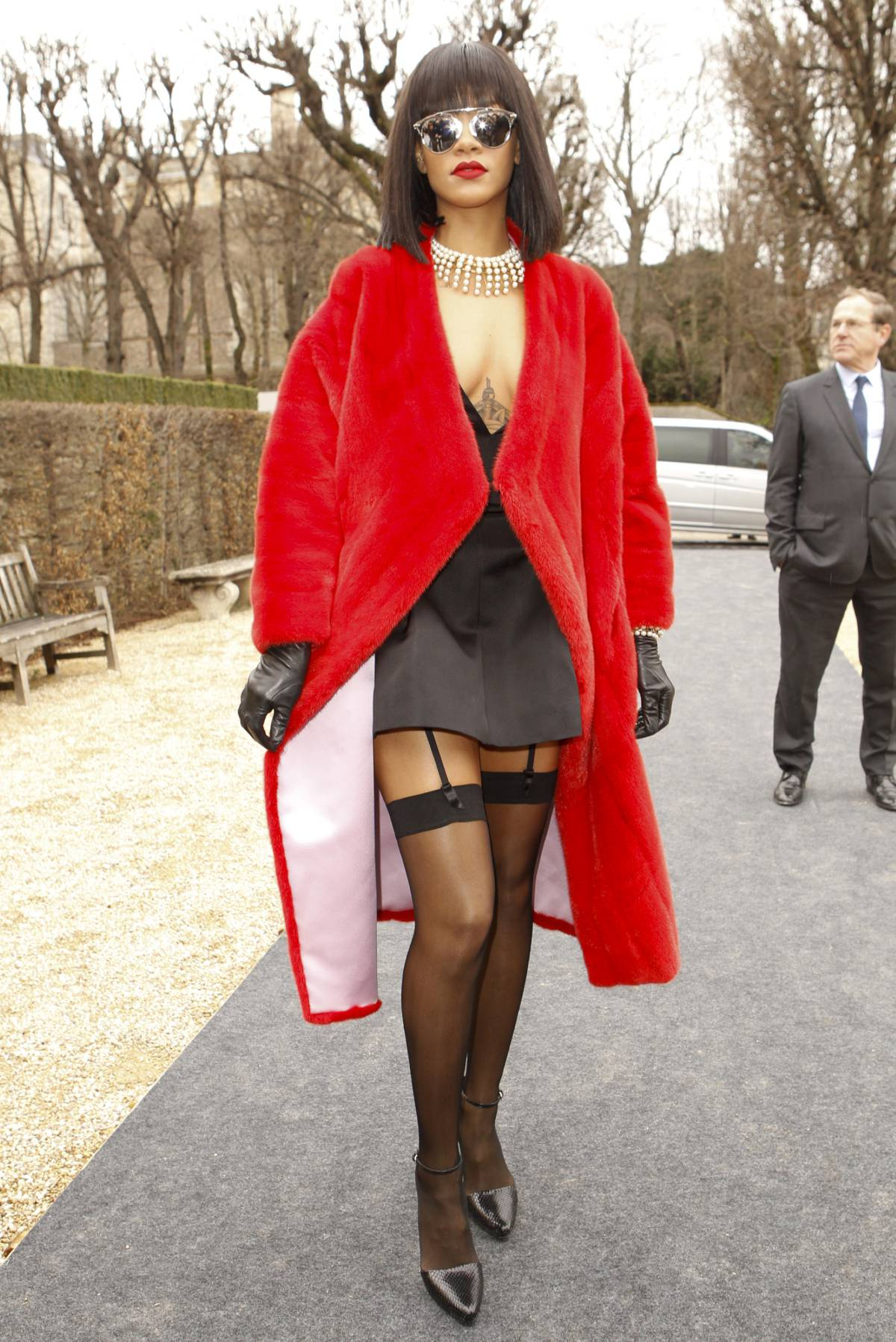 Рианна прилетела на показ Dior в красной норке, чулках и декольте